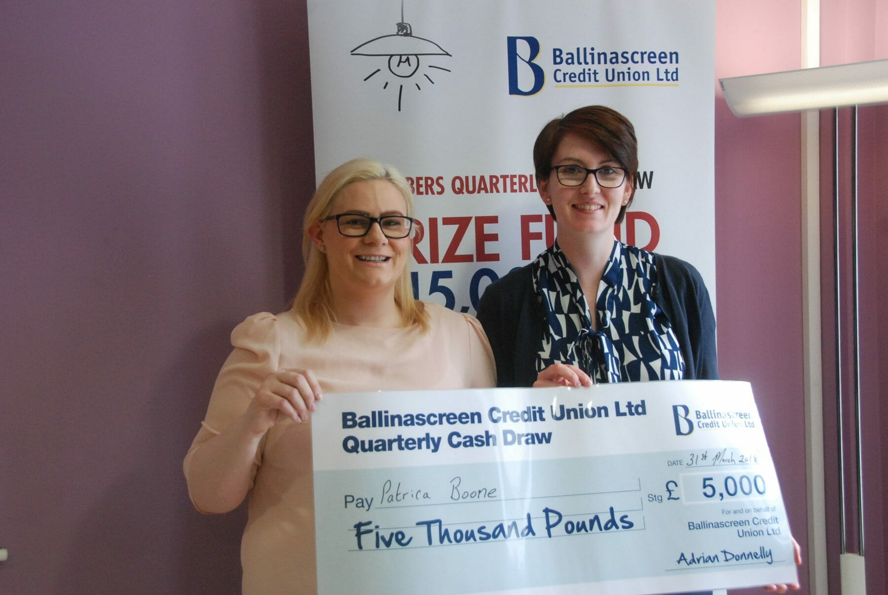 Patricia Boone cash draw winner receiving her cheque from Kathleen O'Hagan